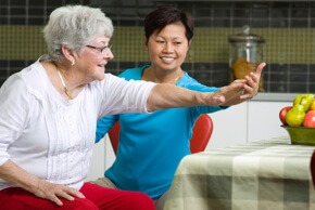 Lady helping an old woman to do physiotherapy